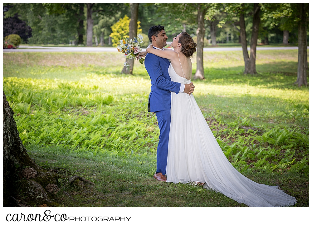a bride in a sleeveless white dress hugs her groom who is wearing a blue suit, during their Maine wedding day first look