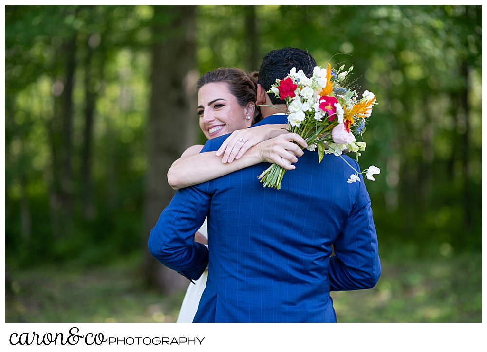 a bride with a bright bouquet, hugs her groom