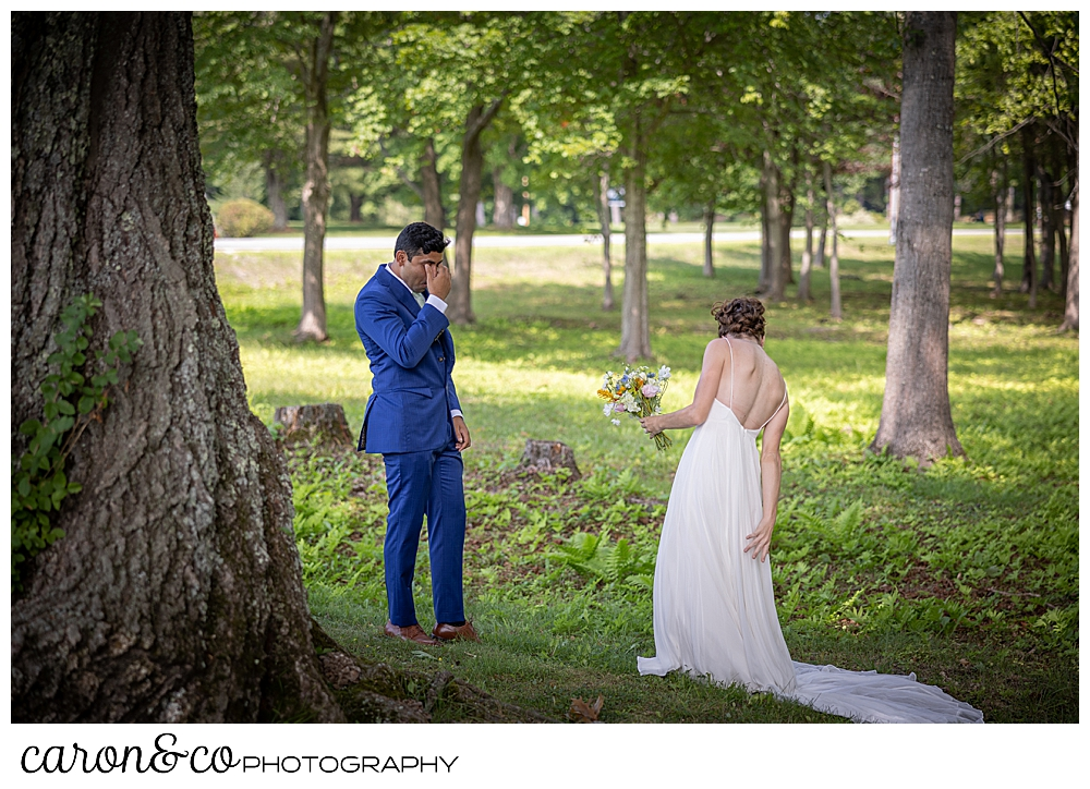 a groom dressed in blue, puts his hand to his eyes, as he views his bride to be during their Maine wedding day first look