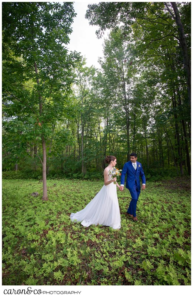 a bride and groom walk together through the woods