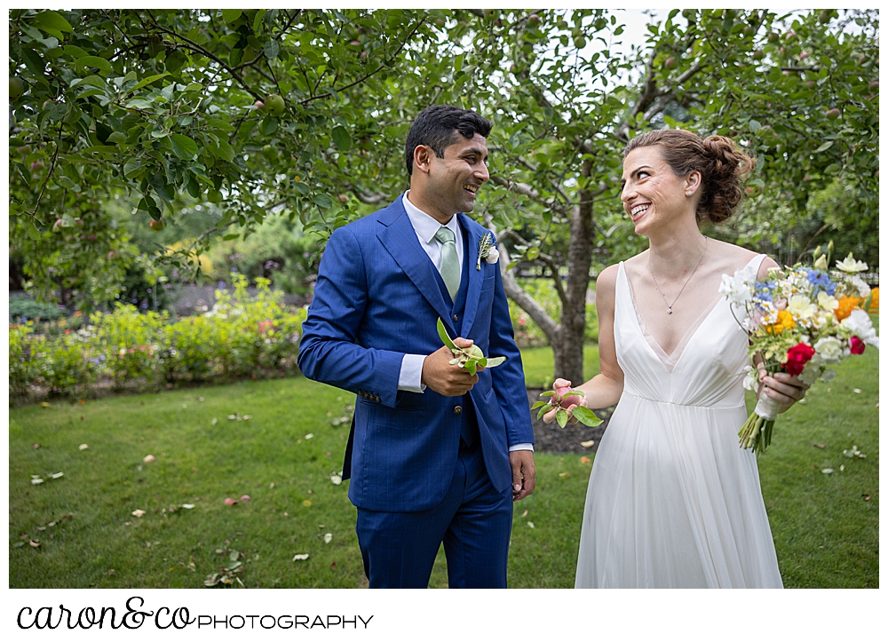 a bride and groom smile at each other while they each hold an apple, at their joyful Pineland Farms wedding