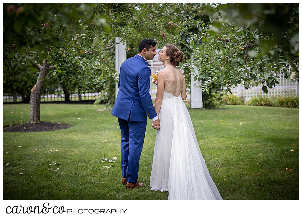 a bride and groom, their backs to the camera, are about to kiss as they walk away