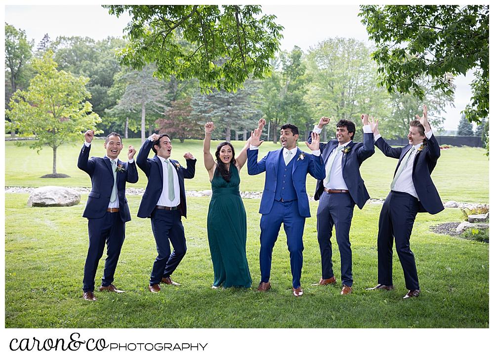 a groom and 4 groomsmen, and 1 groomswoman cheering at a joyful Pineland farms wedding