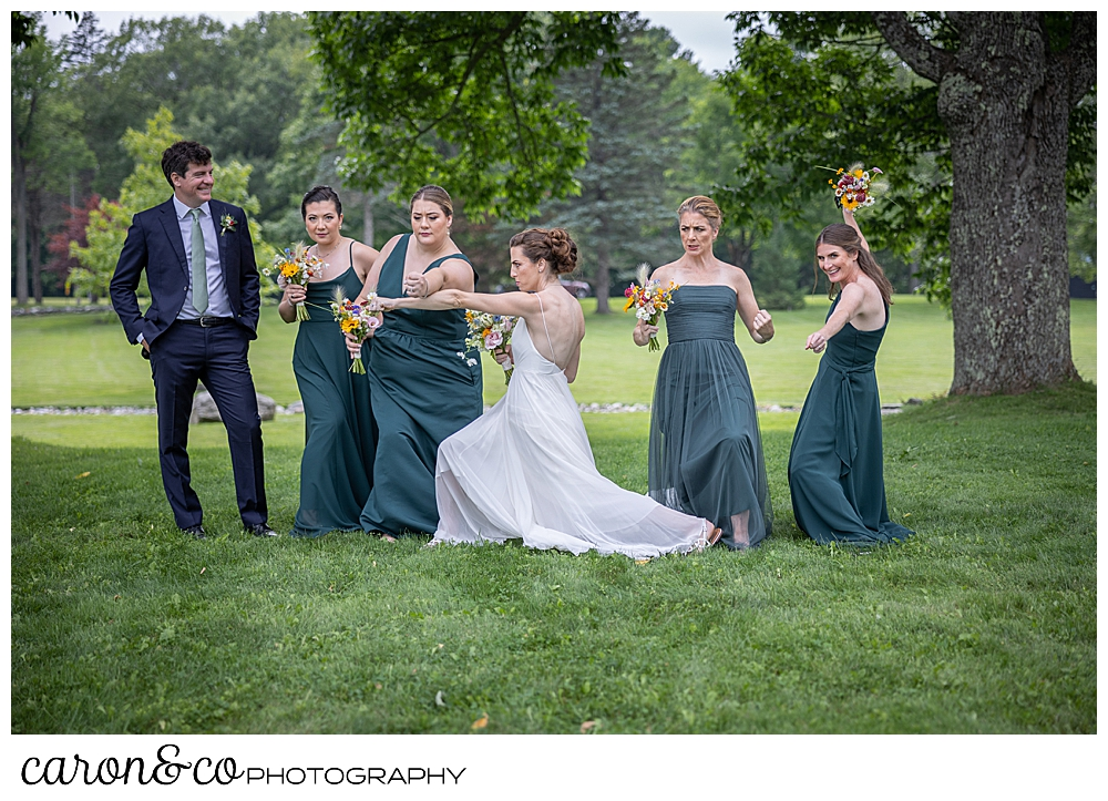 a bride strikes a pose with her 4 bridesmaids, and bridesman