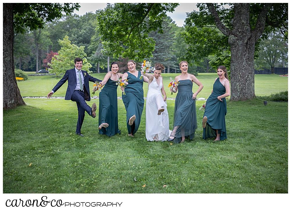 a bride, 4 bridesmaids, and a bridesman dance in a line