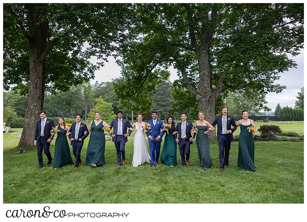 a bridal party with linked arms, walks on the Pineland Farms campus, at a joyful Pineland Farms wedding day