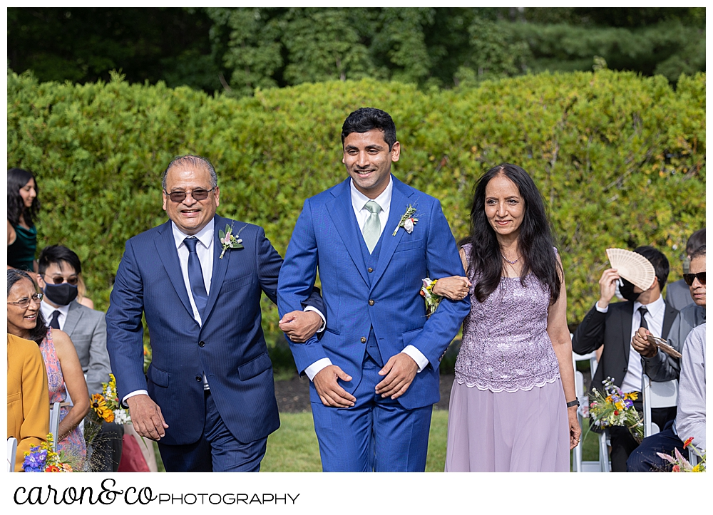 a groom walks down the aisle at the Pineland Farms Garden, with his mother and father