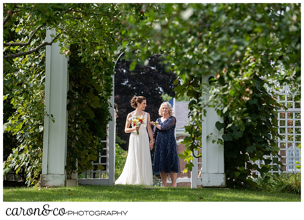 a bride and her mother pause before they enter the Pineland Farms Garden, at a joyful Pineland farms wedding