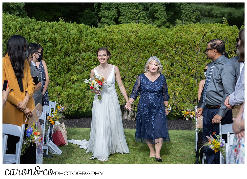 a bride and her mother walk down the aisle at a joyful Pineland Farms wedding in the Garden