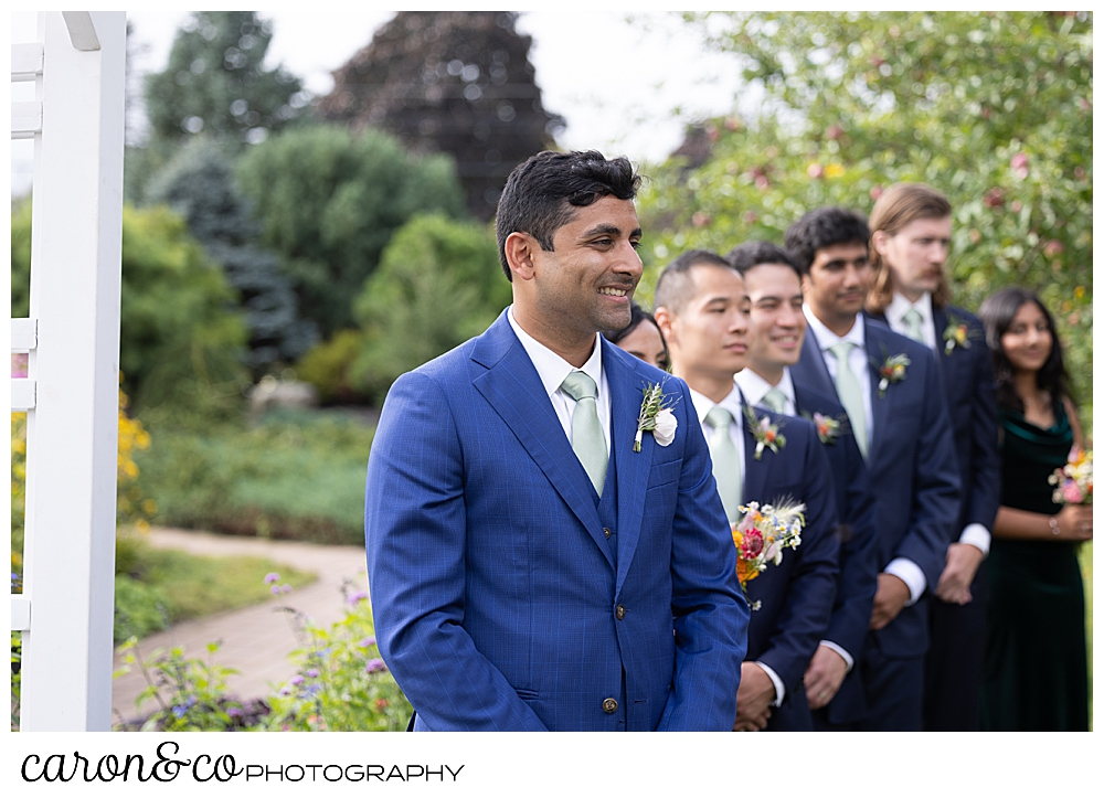 a groom smiles as he waits for the bride to walk down the aisle at a Pineland Farms garden ceremony