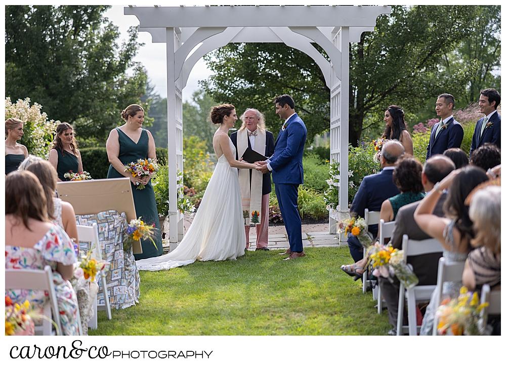 a bride and groom stand under a pergola at a joyful Pineland Farms wedding ceremonh