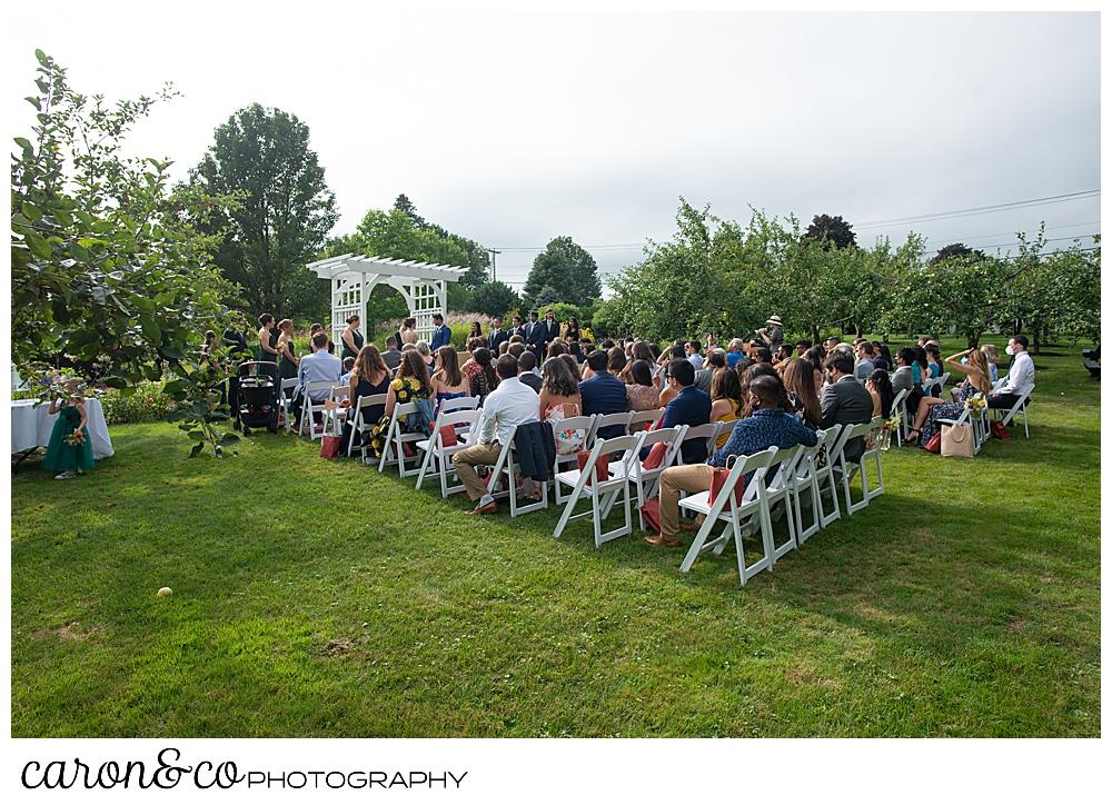 wide view of a joyful Pineland farms wedding ceremony in the garden