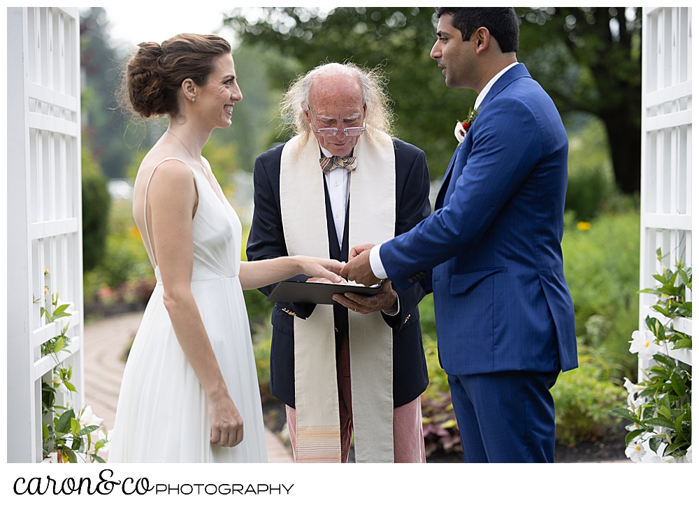 a groom wearing a blue suit, puts a wedding band on a bride wearing a sleeveless white dress, at a joyful Pineland Farms wedding ceremony