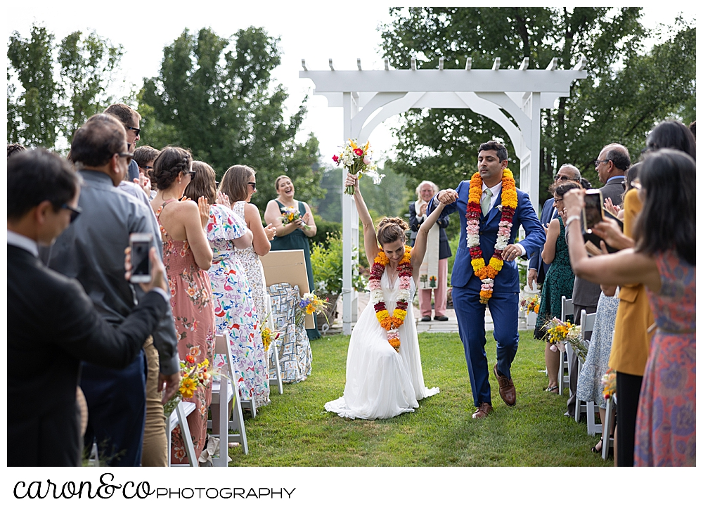 a bride walks down the Pineland farms garden aisle next to her groom, and she bends her knee low to the ground, with her arms up over her head