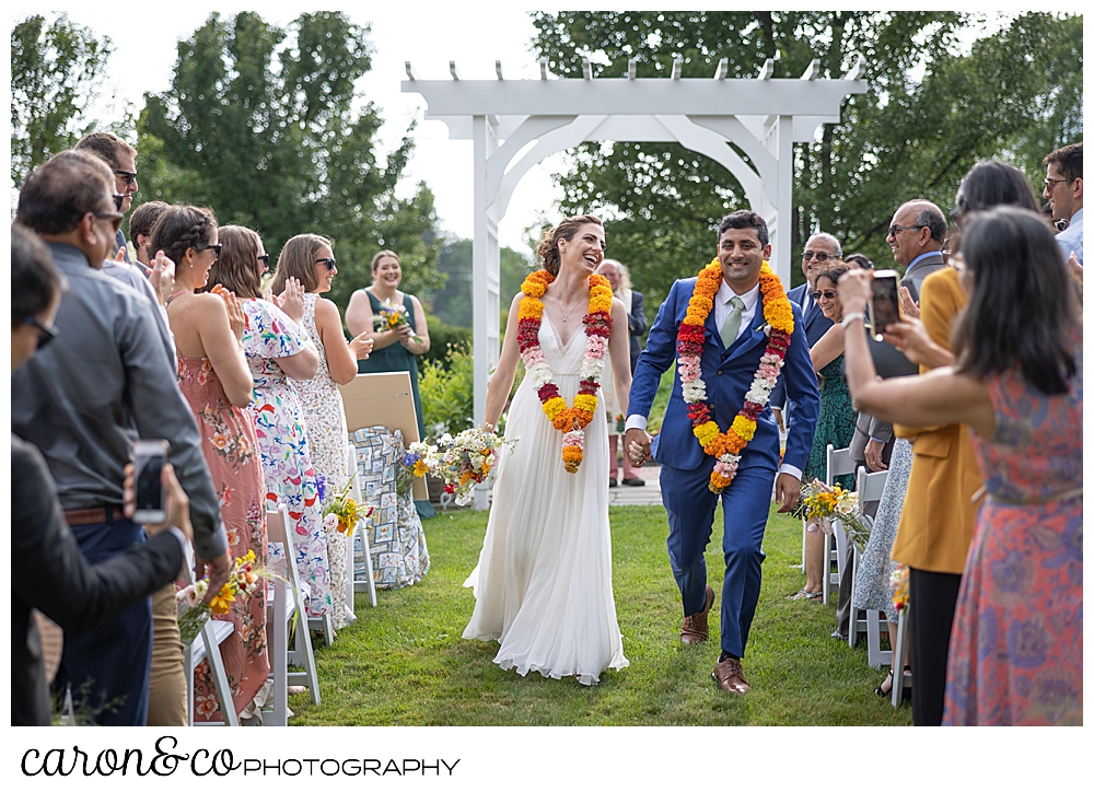 a bride and groom with colorful leis, smile during their recessional at a joyful Pineland farms wedding ceremony