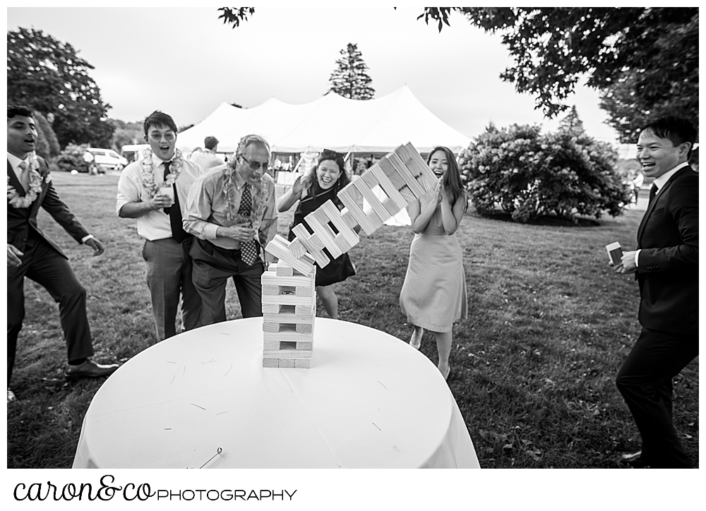black and white photo of wedding guests playing Jenga, and the tower is falling over