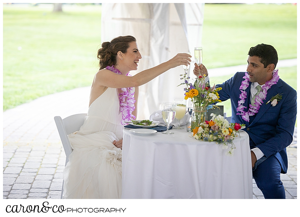 a bride and groom toast with champagne at their tented Pineland Farms wedding reception