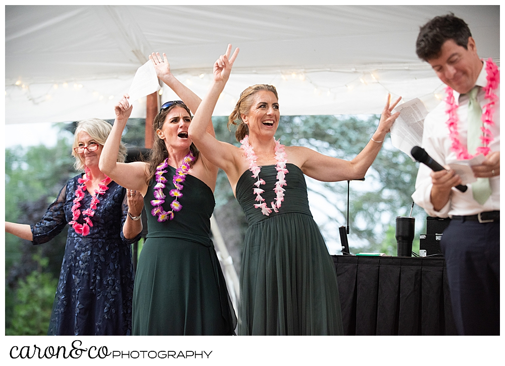 two bridesmaids, a bridesman, and a mother of the bride during wedding reception toasting