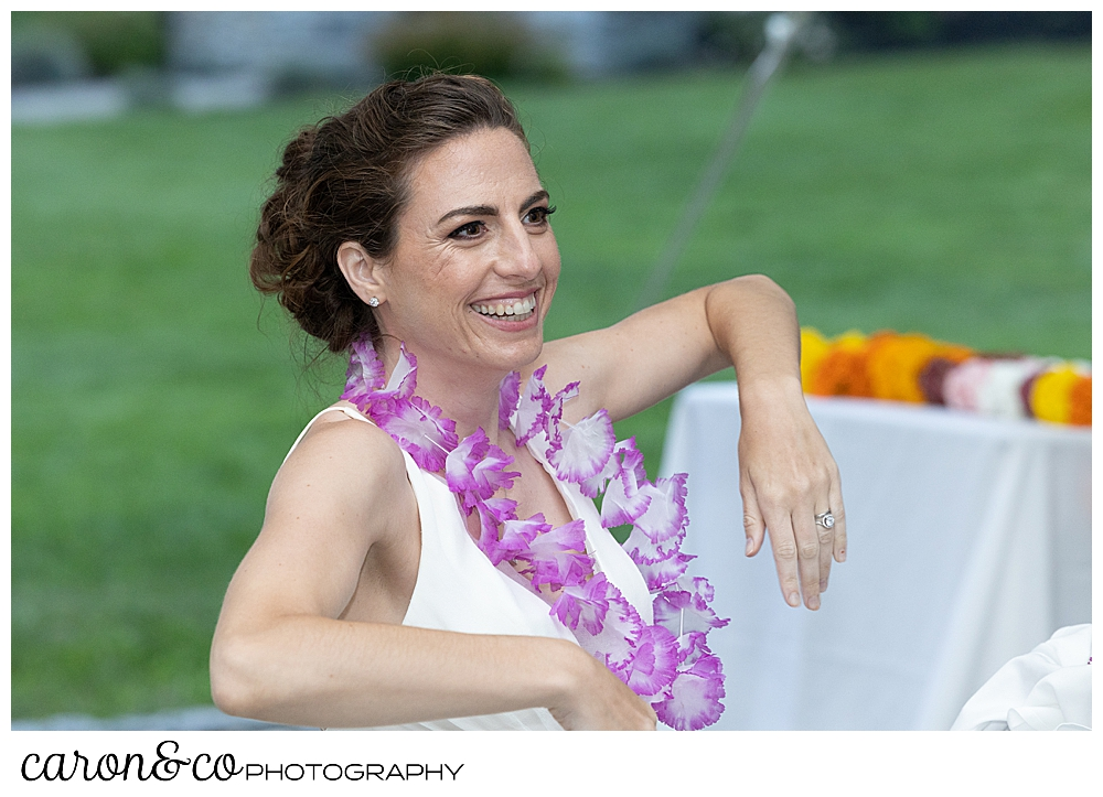 a bride leans her arm on her chair, and smiles at a joyful Pineland Farms wedding reception