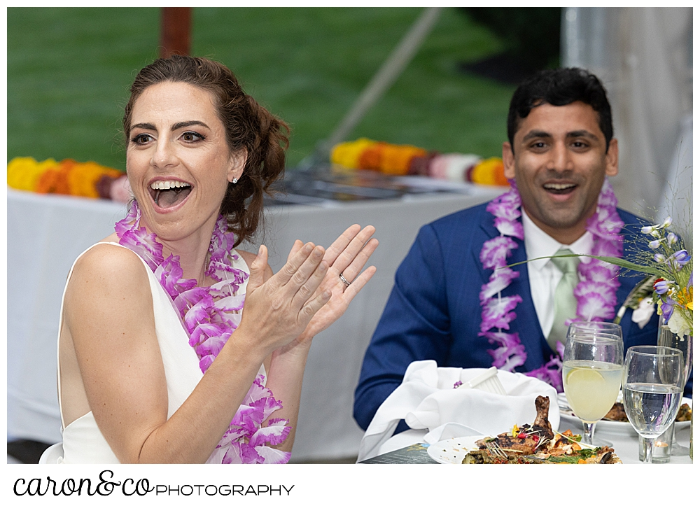 a bride claps, and a groom cheers during a Pineland Farms tented wedding reception
