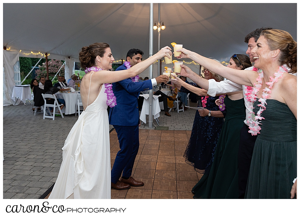 a bride and groom toast with the bride's sisters, mother, and brother