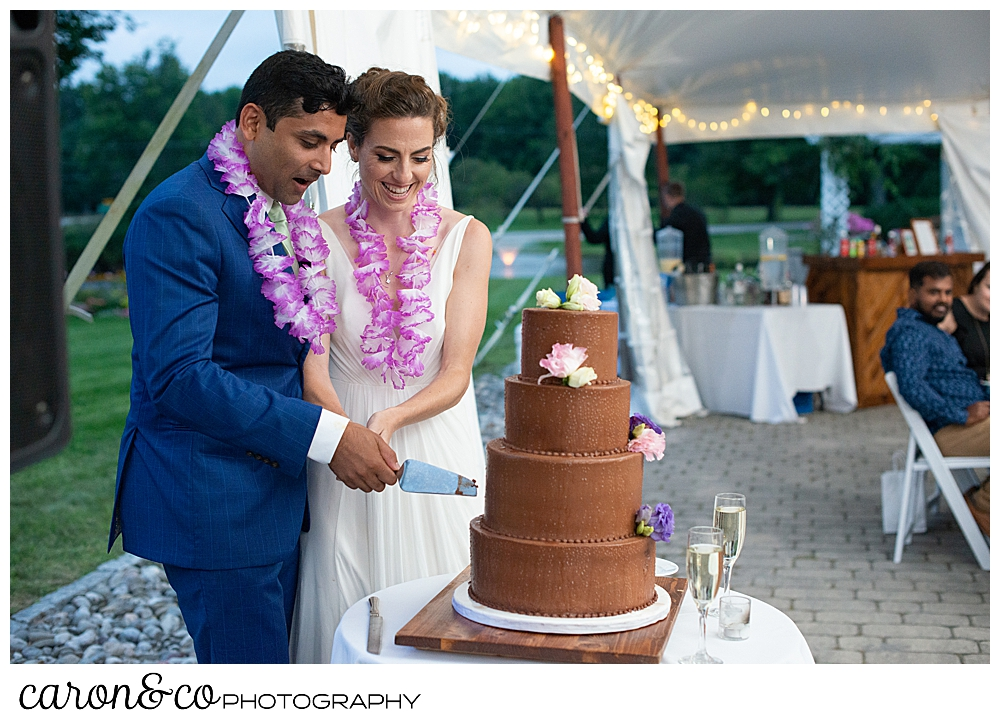 a bride and groom cut a four tiered chocolate wedding cake