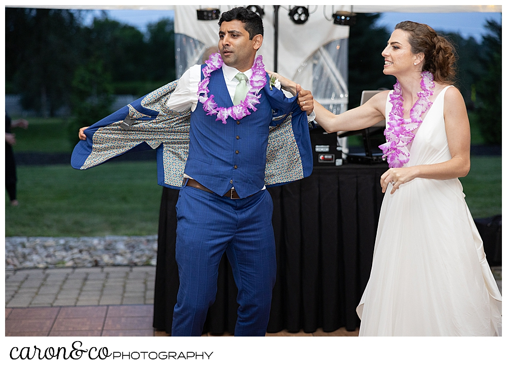 bride and groom during their first dance and the groom starts taking off his jacket