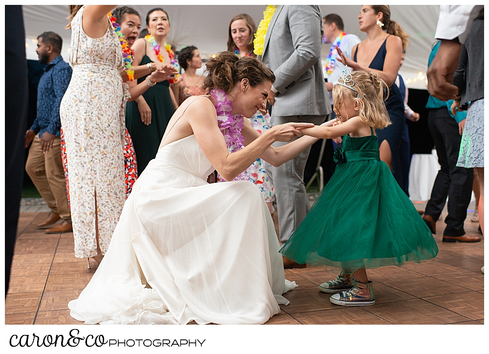 a bride scotching down to dance with a flower girl at a tented Pineland farms wedding