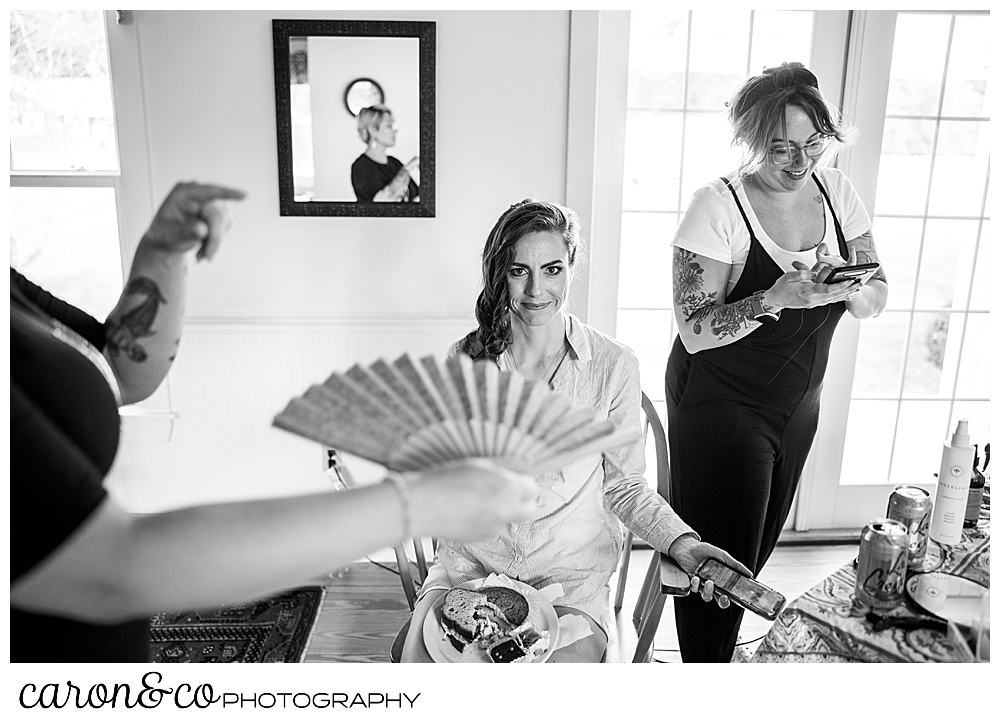 black and white photo of a bride having her hair done, gets fanned while trying to cool off