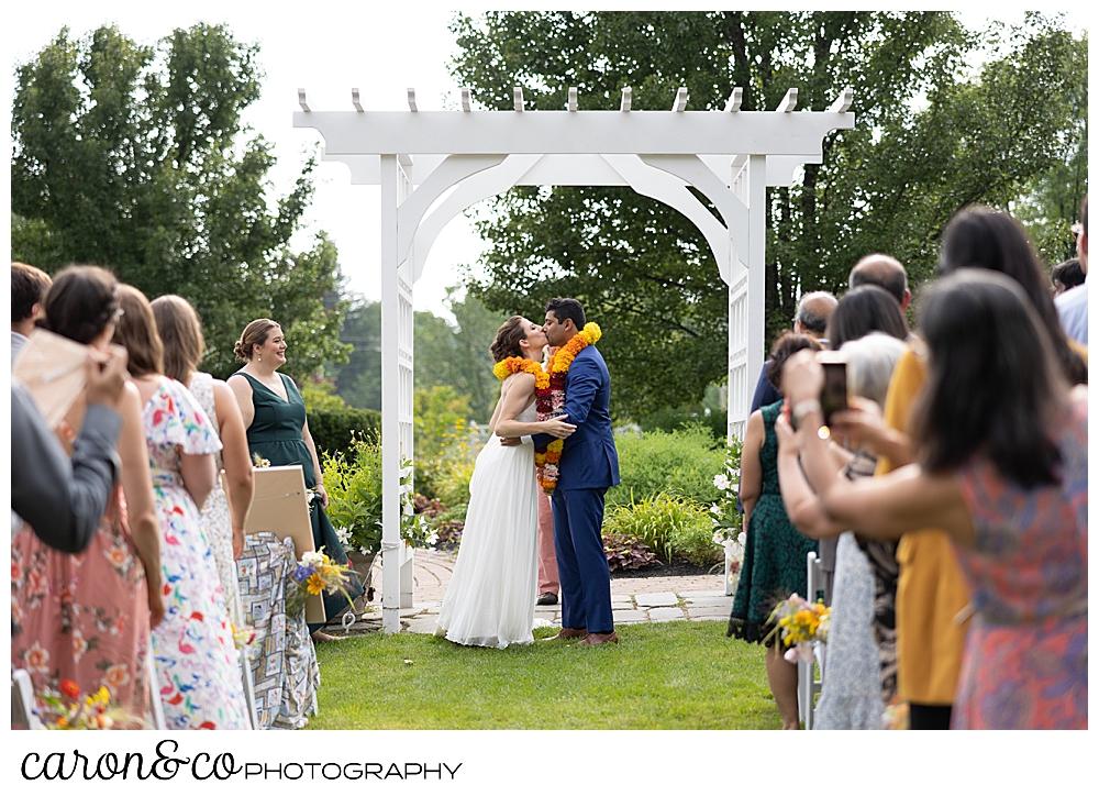a bride and groom share their first kiss under a pergola at their joyful Pineland farms wedding ceremony